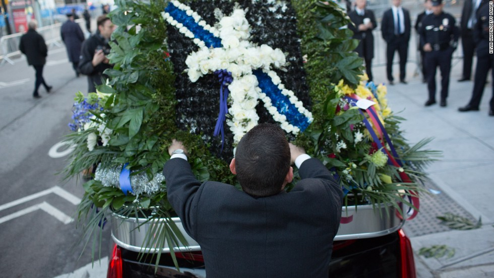 Church staff place flowers on a vehicle before the funeral.