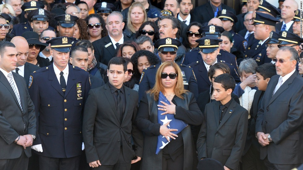Maritza Ramos, center, wife of Officer Ramos, holds the colors as she is flanked by her sons Justin, left, and Jaden during the funeral service.