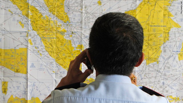 An airport official checks a map of Indonesia at the crisis center set up by local authority for the missing AirAsia flight QZ8501, at Juanda International Airport in Surabaya, East Java, Indonesia, Sunday, Dec. 28, 2014. The AirAsia plane with over 160 people on board lost contact with ground control on Sunday while flying over the Java Sea after taking off from the provincial city in Indonesia for Singapore. (AP Photo/Trisnadi/AP)