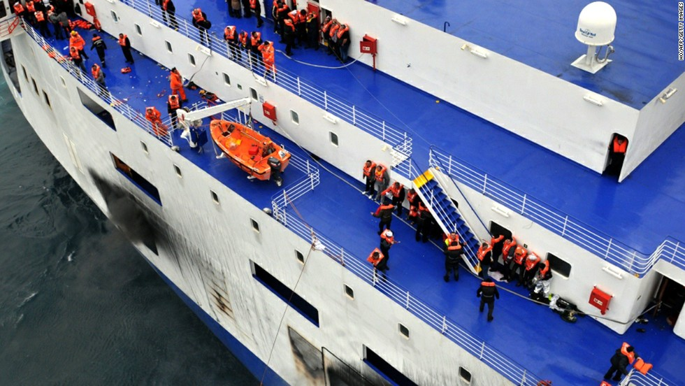 Passengers wait to be rescued from the burning ferry.