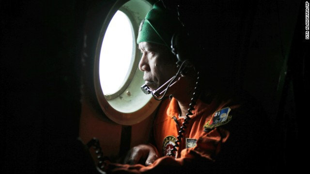 An Indonesian Air Force member looks out of the window of an airplane during a search operation for the missing AirAsia flight 8501 over the waters of Karimata Strait in Indonesia on Monday, December 29.