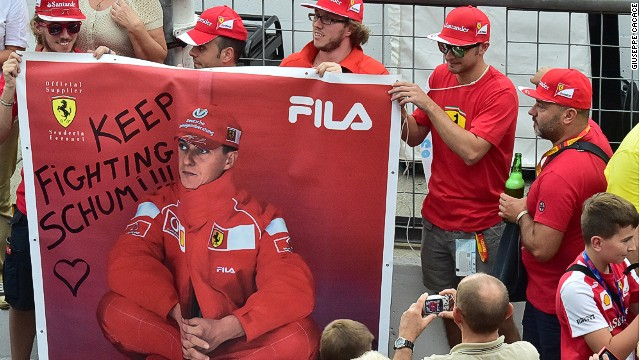 A man takes a photograph of Scuderia Ferrari's supporters as they hold a banner that reads, 'Keep fighting Schumi ' referring to former F1 legend Michael Schumacher, severely injured in December 2013 in a skiing accident in France, at the Autodromo Nazionale circuit in Monza on September 4, 2014 ahead of the Italian Formula One Grand Prix on September 7. AFP PHOTO / GIUSEPPE CACACE