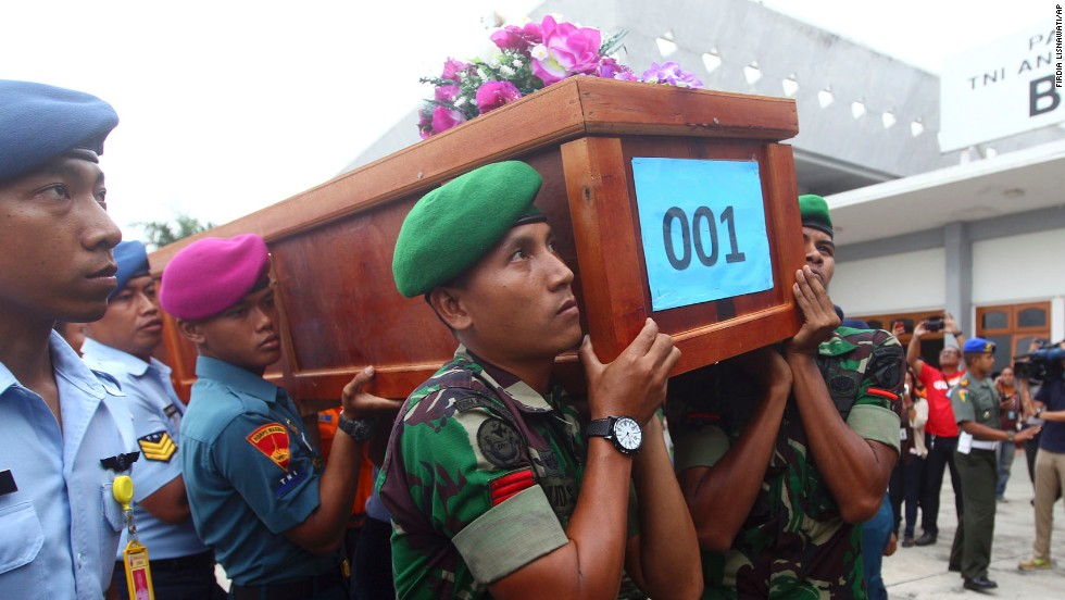 Indonesian soldiers carry a victim's coffin upon arrival at an air force base in Surabaya on Wednesday, December 31.