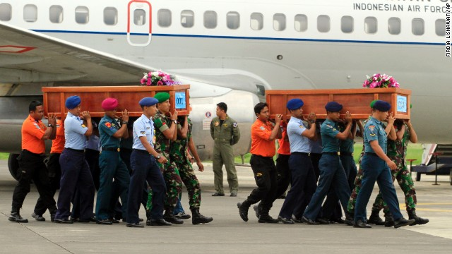 Indonesian soldiers carry coffins on December 31.