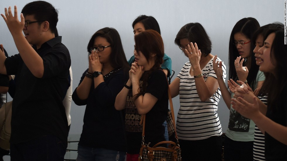 Relatives of passengers pray together inside a holding room at Juanda International Airport in Surabaya on December 31.