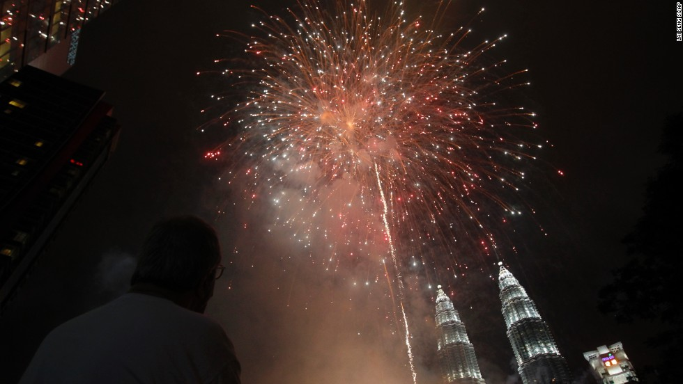 A man watches fireworks explode over Malaysia's landmark Petronas Towers during celebrations in Kuala Lumpur, Malaysia.