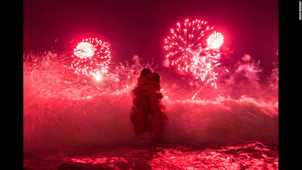A wave crashes as two women hug and fireworks explode over Copacabana beach in Rio de Janeiro early on Thursday, January 1.