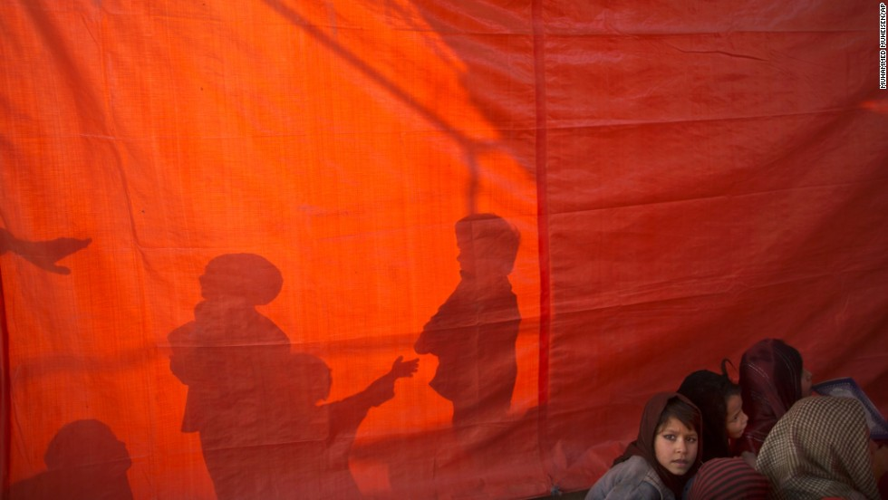 The shadows of Afghan refugee boys are seen on a plastic sheet that is separating their class from a girls' class Monday, December 29, at a makeshift school on the outskirts of Islamabad, Pakistan.