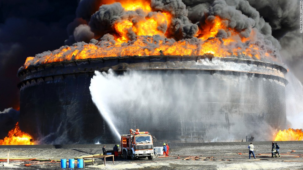 Firefighters spray water at an oil tank in Ras Lanuf, Libya, on Monday, December 29. Oil tanks at the Es Sider port caught fire after one was hit by a rocket during fighting between rival groups.