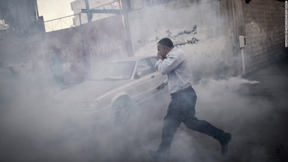 A man runs for cover from tear gas that was fired by police during clashes with protesters Tuesday, December 30, in Bilad al-Qadeem, Bahrain. The protest followed the arrest of Sheikh Ali Salman, leader of the banned Shiite opposition movement Al-Wefaq.