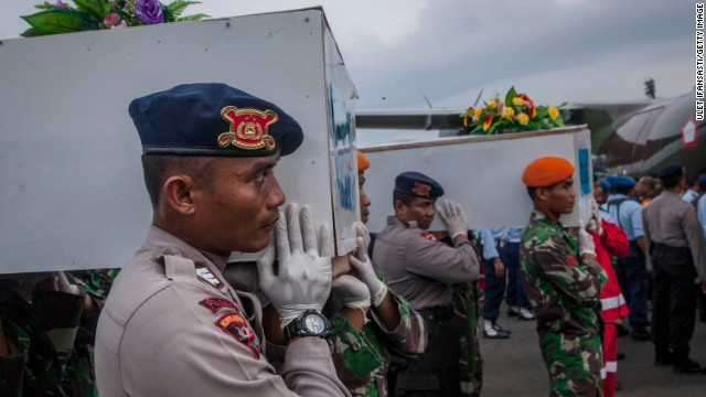 Members of Indonesian search and rescue team carry the coffins containing victims of the AirAsia flight QZ8501 crash boarding to Indonesian airforce aircraft NC295 deliver to Surabaya at Iskandar Airbase on January 02, 2015 in Pangkalan Bun, Central Kalimantan, Indonesia.