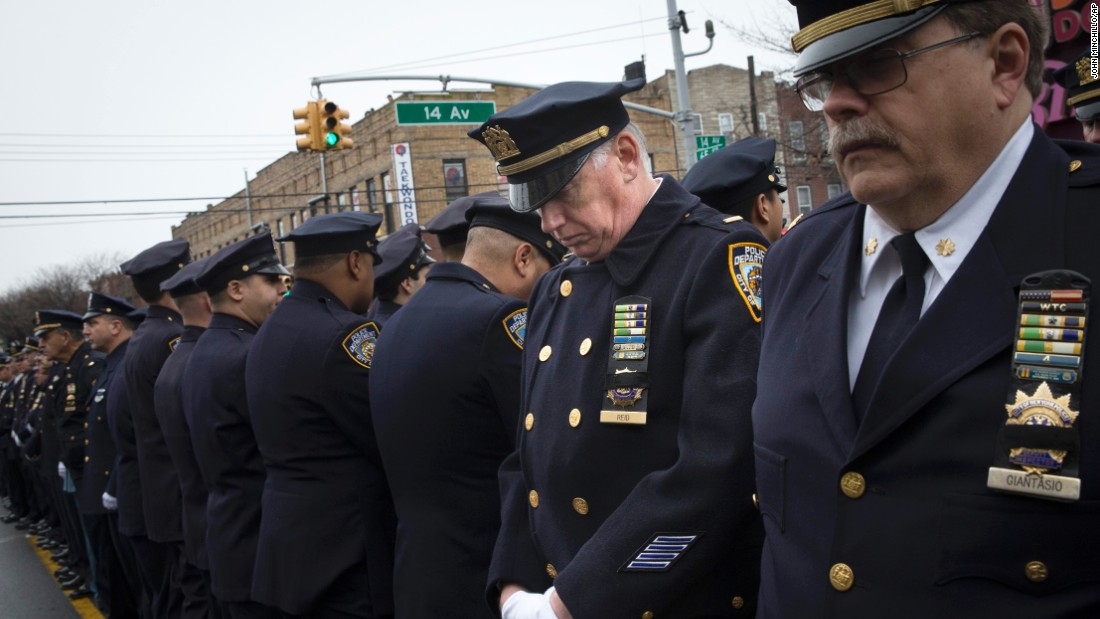 Some police officers turn their backs as de Blasio speaks during the funeral.