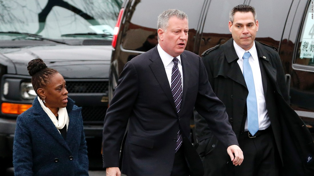 New York City Mayor Bill de Blasio, center, walks with his wife, Chirlane McCray, while arriving for the funeral.