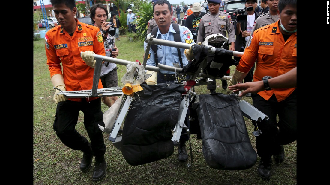 Search and rescue personnel carry seats from the flight on Monday, January 5.