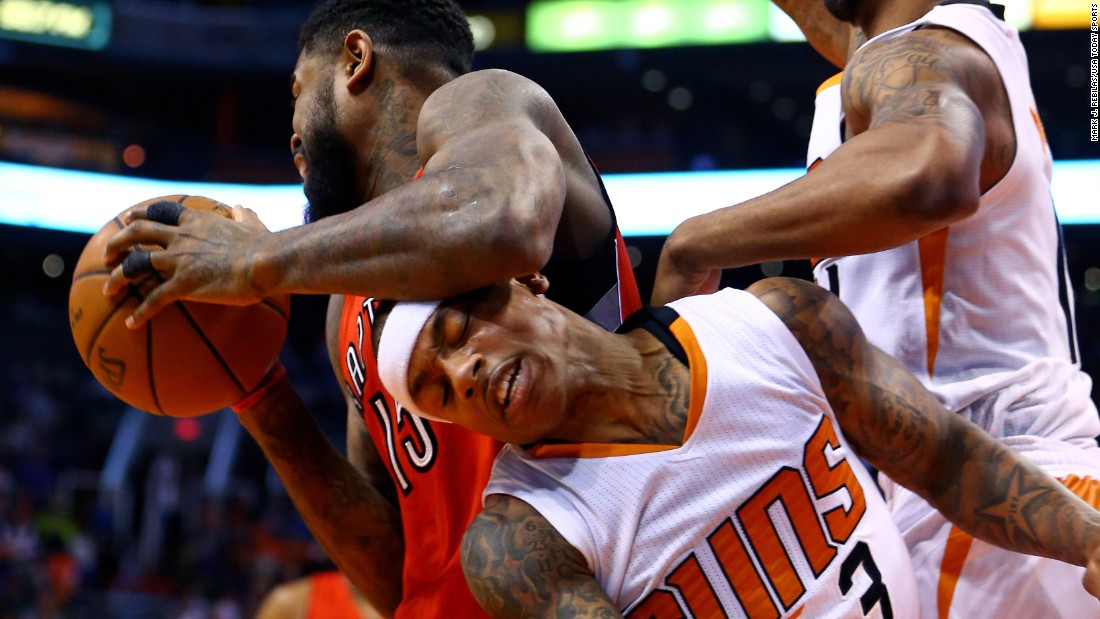 Phoenix Suns guard Isaiah Thomas, center, is fouled by Toronto's Amir Johnson during an NBA game in Phoenix on Sunday, January 4.