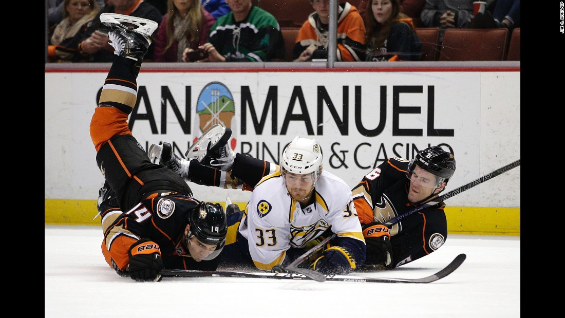 Nashville's Colin Wilson, center, falls to the ice along with Anaheim's Rene Bourque, left, and Ben Lovejoy during an NHL game Sunday, January 4, in Anaheim, California. The Ducks won 4-3 in overtime to improve their record to a league-best 26-9-6.