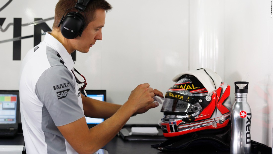 Fitness trainers are are multitaskers. Here, Antti Vierula, the former personal trainer for McLaren's Kevin Magnussen, tinkers with the Dane's helmet prior to a race weekend.
