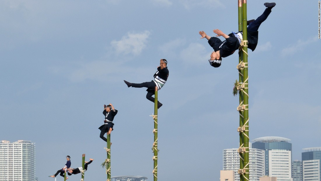 JANUARY 6 - TOKYO, JAPAN: Members of the Edo Firemanship Preservation Association wearing traditional firefighting uniforms perform ladder stunts during the Tokyo Fire Department's new year fire review. About 2,700 firefighters participated in the annual exercises.