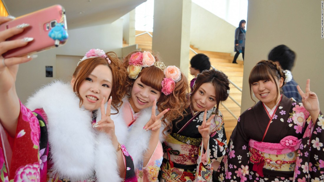 Young women in kimonos take a photo during a coming-of-age ceremony Saturday, January 3, in Otawara, Japan.