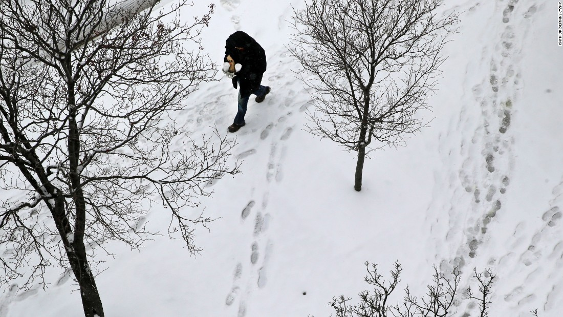 A man walks on a snow-covered sidewalk on Tuesday, January 6, in Baltimore. <br />