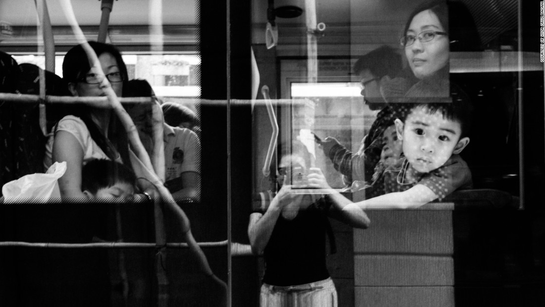 "Bacani catches her reflection on a bus in Causeway Bay, one of Hong Kong's busiest shopping districts. She has lived in the city for nine years and still doesn't feel like she belongs. ""When you're a helper, you don't have a right to be a photographer,"" she says."