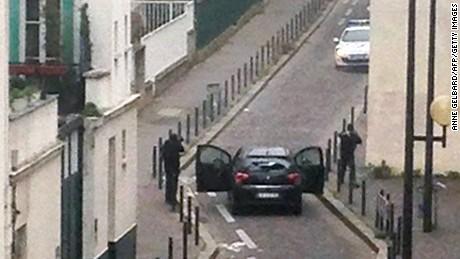 Armed gunmen face police officers near the offices of the French satirical newspaper Charlie Hebdo in Paris on January 7.