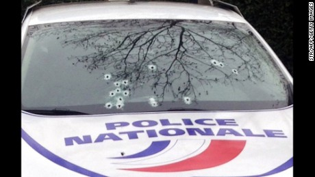 A police car sitts riddled with bullets.