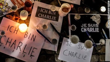 "Papers with ""I am Charlie"" written in various languages are left near candles at a vigil on January 7 in front of the French Embassy in Berlin."