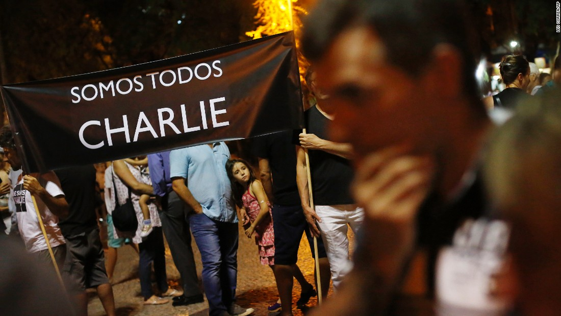 "People in Rio de Janeiro hold a sign that reads ""We're all Charlie"" on January 7."