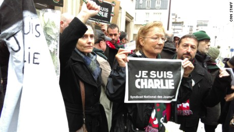 People take to the streets in Paris for a vigil to honor victims of the attack on Charlie Hebdo magazine.