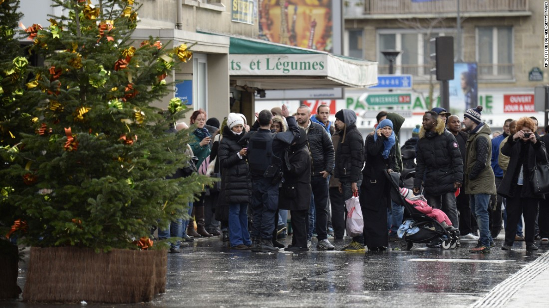 A police officer gives instructions to local residents in Saint-Mande, which is near Porte de Vincennes.