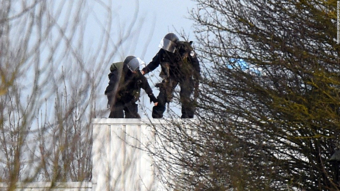 Police take position on a roof during the standoff.