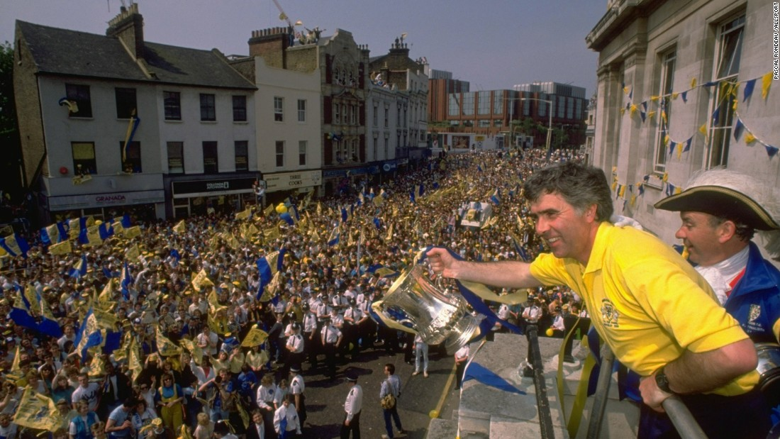 "Manager Bobby Gould, seen showing off the trophy to Wimbledon's fans, has described the 1988 squad as being like ""the worst school(boys) in England."""