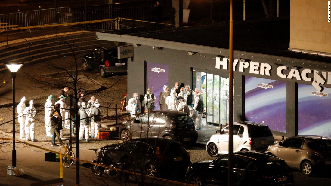 Forensics investigators gather outside the grocery store. French President Francois Hollande said four people were killed.