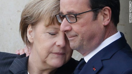 French President Francois Hollande embraces German Chancellor Angela Merkel as she arrives at Elysee Palace before the rally.