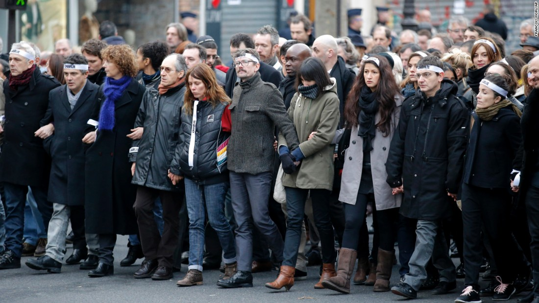 Luzier, center with mustache, marches with other survivors of the Charlie Hebdo massacre as well as family members of victims.