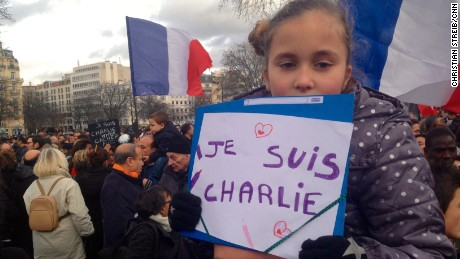 A little girl holds up a sign while sitting on the shoulders of a man at the Paris unity rally.