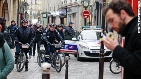 Police officers patrol Rue des Rosiers street on bicycle, in the heart of the Paris Jewish quarter, Monday Jan. 12, 2015. France on Monday ordered 10,000 troops into the streets to protect sensitive sites after three days of bloodshed and terror, amid the hunt for accomplices to the attacks that left 17 people and the three gunmen dead. (AP Photo/Remy de la Mauviniere/AP)