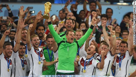 Germany keeper Neuer  lifts the World Cup trophy with his team after defeating Argentina 1-0 in the 2014 World Cup final.