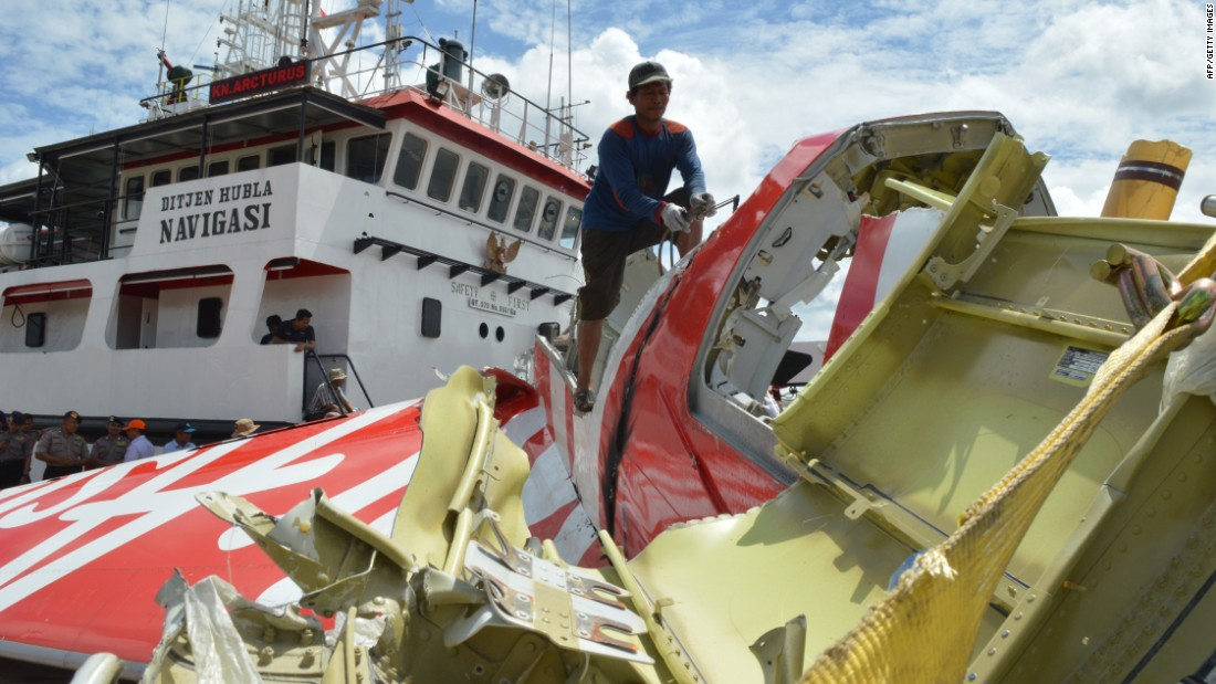An Indonesian worker cuts part of the plane's tail January 12 after debris from the crash was retrieved from the Java Sea.