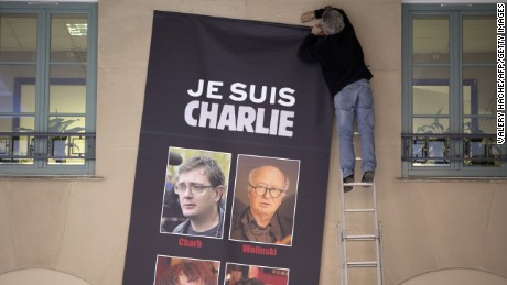 A man puts up a banner reading 'Je suis Charlie' (I am Charlie) featuring the portraits of late Charlie Hebdo editor Stephane Charbonnier (aka Charb) and late French cartoonists Georges Wolinski, Jean Cabut (aka Cabu), Bernard Verlhac (aka Tignous) in Nice, southeastern France on January 8, 2015, after armed gunmen attacked the offices of French satirical newspaper Charlie Hebdo in Paris on January 7, leaving 12 dead. A stunned and outraged France was in mourning yesterday, as security forces desperately hunted two brothers suspected of gunning down 12 people in an Islamist attack on a satirical weekly. AFP PHOTO / VALERY HACHE (Photo credit should read VALERY HACHE/AFP/Getty Images)