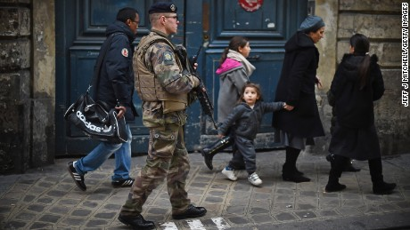 PARIS, FRANCE - JANUARY 12: Armed security patrol outside a Jewish School in the Jewish quarter of the Marais district as children make their way home on January 12, 2015 in Paris, France. Mr Cazeneuve visited the area to inspect the deployment of thousands of troops and police to bolster security at 'sensitive' sites including Jewish schools. An estimated one million people converged in central Paris yesterday for a Unity March joining in solidarity with the 17 victims of last week's terrorist attacks in the country. French President Francois Hollande led the march and was joined by world leaders in a sign of unity. The terrorist atrocities started on Wednesday with the attack on the French satirical magazine Charlie Hebdo, killing 12, and ended on Friday with sieges at a printing company in Dammartin en Goele and a Kosher supermarket in Paris with four hostages and three suspects being killed. A fourth suspect, Hayat Boumeddiene, 26, escaped and is wanted in connection with the murder of a policewoman. (Photo by Jeff J Mitchell/Getty Images)