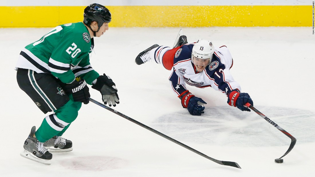 Cam Atkinson of the Columbus Blue Jackets dives for control of the puck while playing Cody Eakin and the Dallas Stars on Tuesday, January 6.
