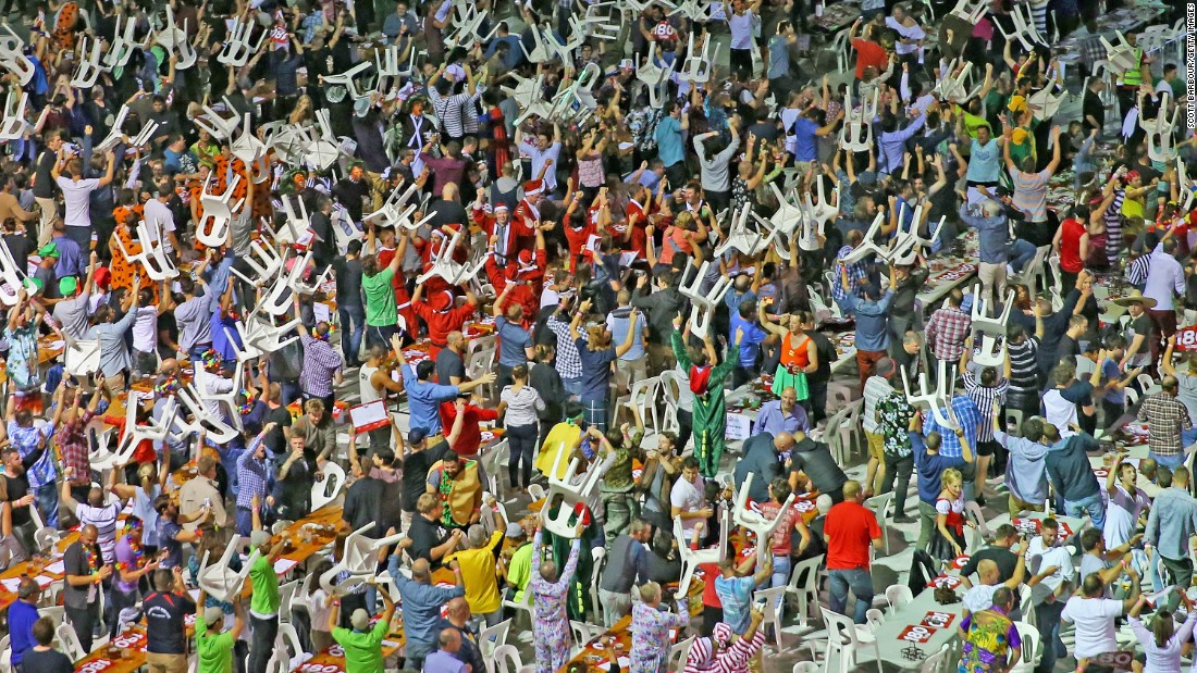 "Fans raise plastic chairs above their heads during the final of the Invitational Darts Challenge, which took place Saturday, January 10, in Melbourne. Some fans <a href=""http://www.washingtonpost.com/blogs/early-lead/wp/2015/01/10/international-darts-tournament-in-australia-gets-insane-when-fans-start-massive-brawl/"" target=""_blank"">threw their chairs</a> at one another, starting a fight."