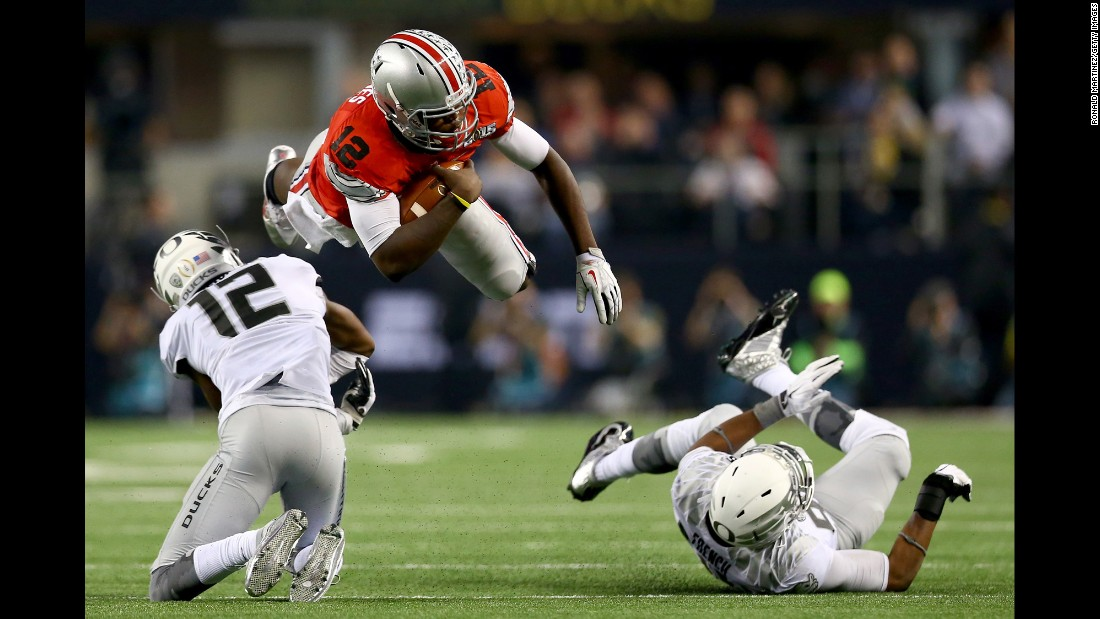 Ohio State quarterback Cardale Jones dives over two Oregon defenders during the national championship game Monday, January 12.