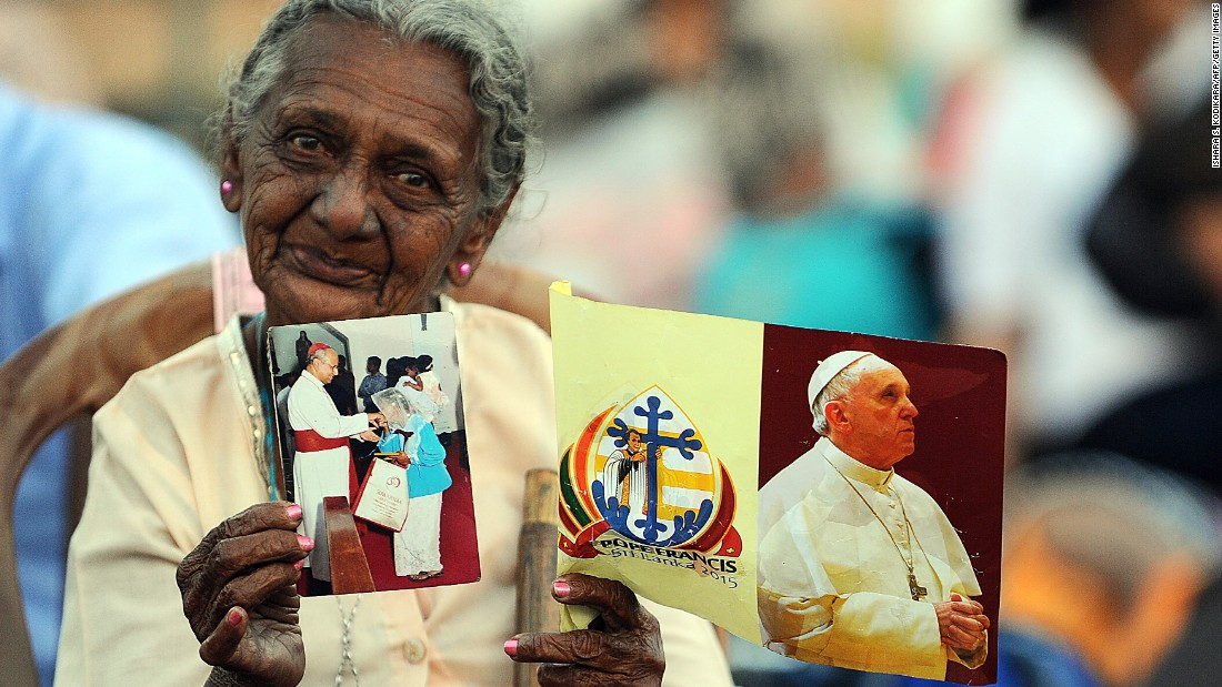 A Sri Lankan woman holds a flag bearing a portrait of Pope Francis.