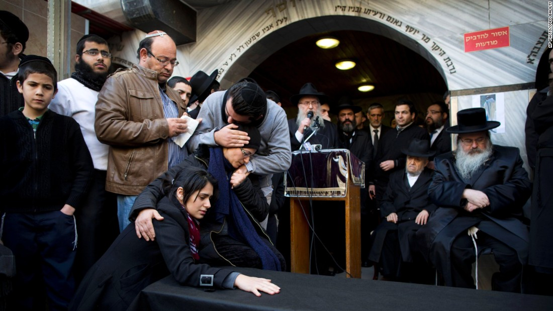 The family of Hattab gather around a symbolic coffin for his funeral procession in the city of Bnei Brak near Tel Aviv.