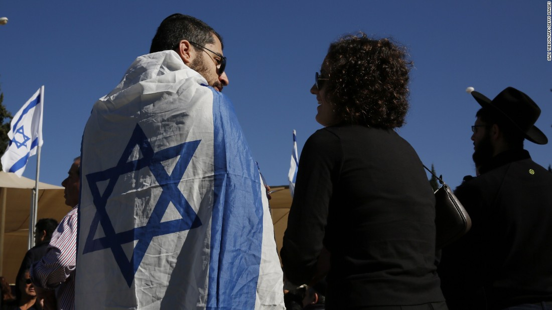 An Israeli man wrapped in a national flag joins family members and other mourners at the funeral.
