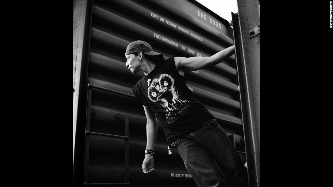 A Salvadoran migrant hangs off the back of a cargo train in Arriaga, Mexico, in July 2010.
