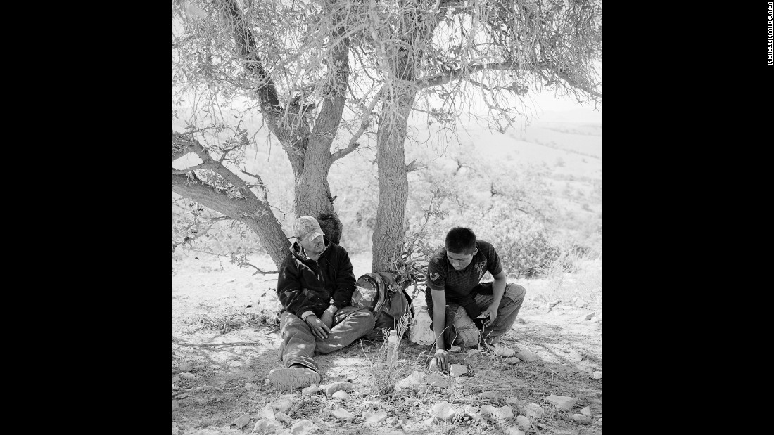 Migrants rest in the shade of a mesquite tree in May 2012.